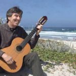 Arnie Gamble playing classical guitar at the beach.